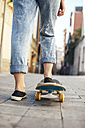 Young female skate boarder on her skateboard, partial view - EBSF000286