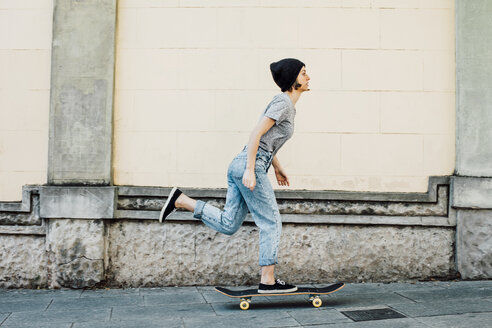 Young female skate boarder driving with her skateboard - EBSF000299