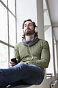 Portrait of young man sitting on window sill in an office listening music with headphones - RBF001693