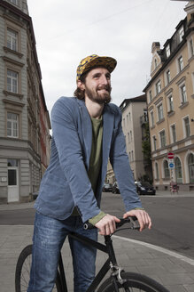 Germany, Bavaria, Munich, smiling young man wearing basecap standing on pavement with his racing cycle - RBF001702
