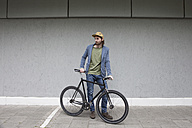 Germany, Bavaria, Munich, young man wearing basecap standing in front of a wall with his racing cycle - RBF001705