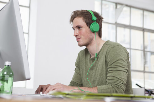 Portrait of smiling young man working at computer while listening music with headphones - RBF001711