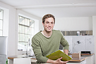 Portrait of smiling young man sitting on his desk in the office - RBF001787