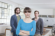 Portrait of young woman with her two colleagues in the background standing in a creative office - RBF001742