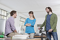 Three colleagues talking together in an office - RBF001749
