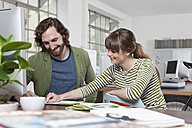 Two colleagues working together in a creative office - RBF001758