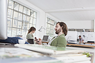 Young man sitting at his desk in a creative office using his smartphone - RBF001765