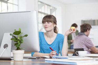 Portrait of young woman eating an apple at her desk in a creative office - RBF001795