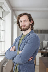Portrait of a man with crossed arms in a creative office - RBF001779