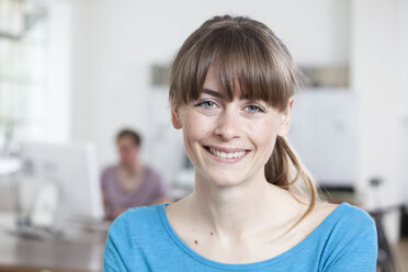 Portrait of smiling young woman in an creative office - RBF001782