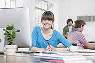 Portrait of smiling young woman sitting at her desk in a creative office - RBF001785