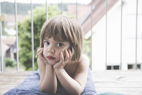 Portrait of sad little girl lying on towel on balcony - LVF001747