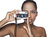 Portrait of woman holding camera in front of white background - KDF000485