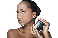 Portrait of woman holding camera in front of white background - KDF000487