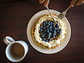Person eating fresh baked waffles with blueberries and whipped cream - ABAF001449