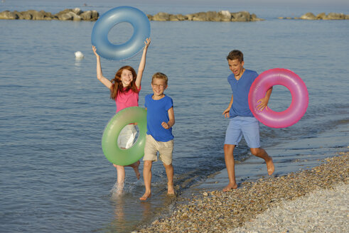Three children running at waterside of Adria with their floating tires - LBF000892
