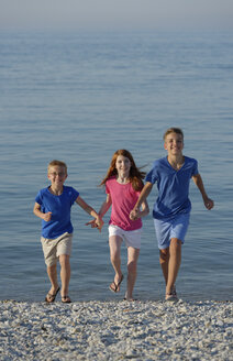 Italy, three smiling children running hand in hand on stony beach in front of the sea - LBF000894