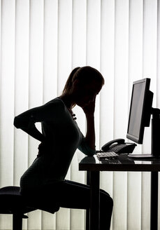 Silhouette of woman at desk having back pain - EJWF000457