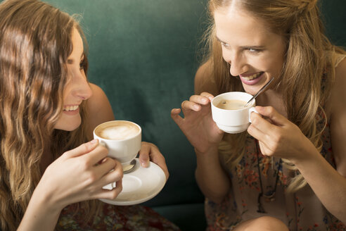 Two female friends having fun in a coffee shop - FCF000383