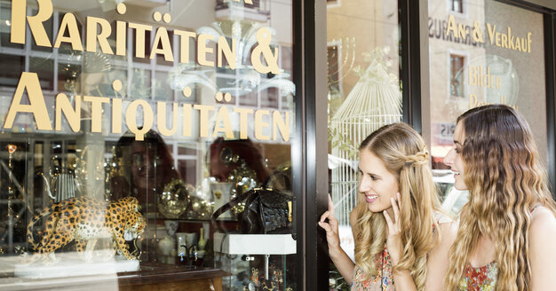 Two female friends standing in front of the window of an antique shop - FCF000390