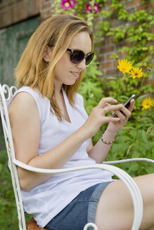Young woman with sunglasses sitting in a garden using her smartphone - SEF000805