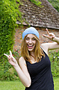 Portrait of smiling young woman with blue bonnet showing victory-sign with both hands - SEF000810