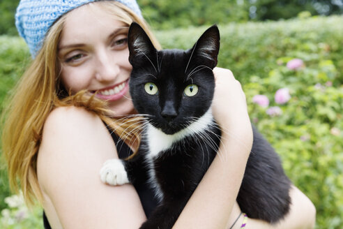Portrait of a smiling young woman holding cat on her arms - SEF000831