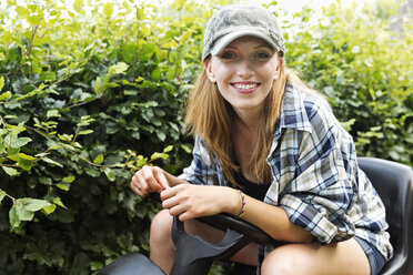 Portrait of a smiling young woman sitting on a lawn-mower - SEF000835