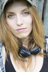 Portrait of a young woman with cap and headphones around her neck - SEF000823
