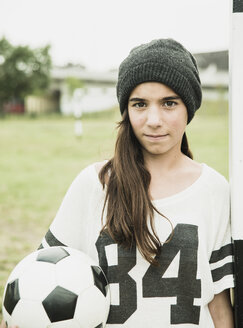 Portrait of teenage girl with soccer ball leaning at goalpost - UUF001558