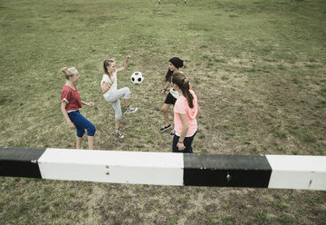 Four teenage girls playing soccer on a football ground - UUF001560