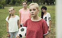 Portrait of serious looking teenage girl with soccer ball in front of three other girls - UUF001564