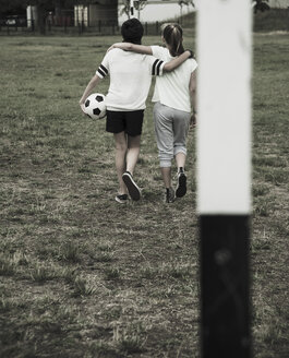 Two teenage girls walking on a football ground, back view - UUF001566