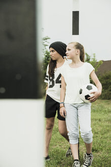 Two teenage girls with soccer ball standing on a football ground - UUF001588