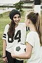 Two teenage girls communicating on a football ground - UUF001568