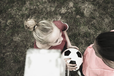 Two teenage girls communicating on a football ground, elevated view - UUF001570