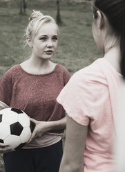 Two teenage girls communicating on a football ground, partial view - UUF001574