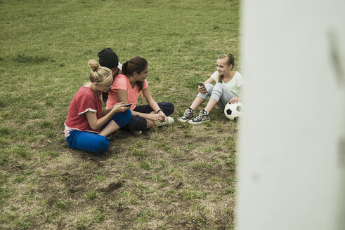 Four female teenage friends sitting on soccer field using their smartphones - UUF001580