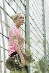Teenage girl with skateboard leaning at fence - UUF001581