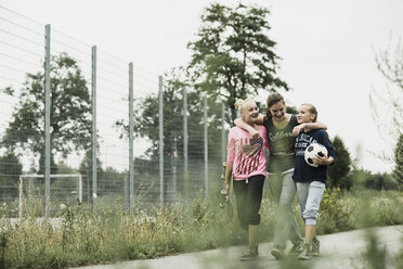 Three teenage girls with soccer ball and skateboard walking side by side - UUF001583