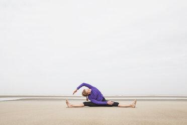 Belgium, Flanders, woman doing yoga exercises on the beach - GW003711