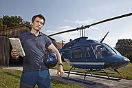 Germany, Bavaria, Landshut, Helicopter pilot holding map - KDF000061