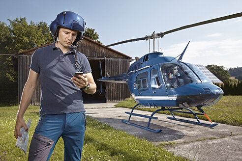 Germany, Bavaria, Landshut, Helicopter pilot using mobile phone - KDF000064