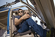 Germany, Bavaria, Landshut, Helicopter pilot sitting in open helicopter, waiting - KDF000040