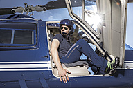 Germany, Bavaria, Landshut, Helicopter pilot sitting in open helicopter, waiting - KDF000082