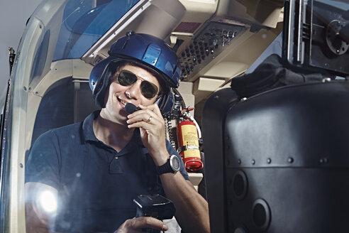 Germany, Bavaria, Landshut, Helicopter pilot in cockpit - KDF000044