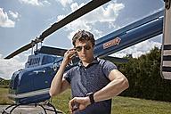Germany, Bavaria, Landshut, Helicopter pilot using mobile phone - KDF000076