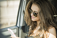 Portrait of smiling teenage girl with sunglasses sitting in a car watching her smartphone - UUF001592