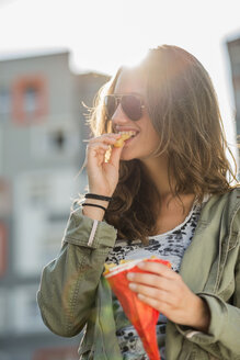 Portrait of teenage girl wearing sunglasses eating French Fries - UUF001597