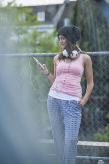Portrait of smiling teenage girl with smartphone and headphones leaning at wire fence - UUF001632